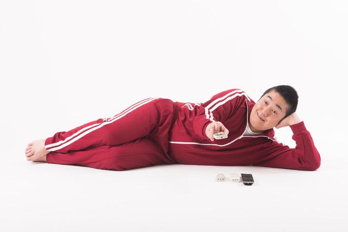 寝転がってテレビを見る男性